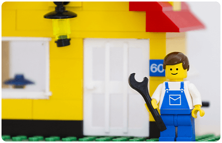 a lego house with a lego man in front of it holding a lego wrench.