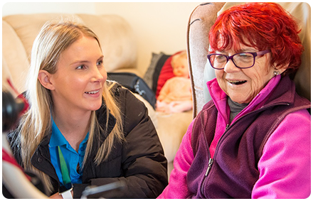 a rocky bay disability support worker and client sit together and are smiling.