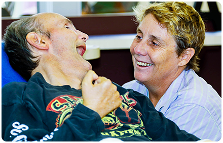 a rocky bay disability support worker and a client smile together in shared disability housing.
