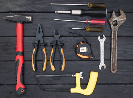 a black wooden table has a range of tools displayed on it.