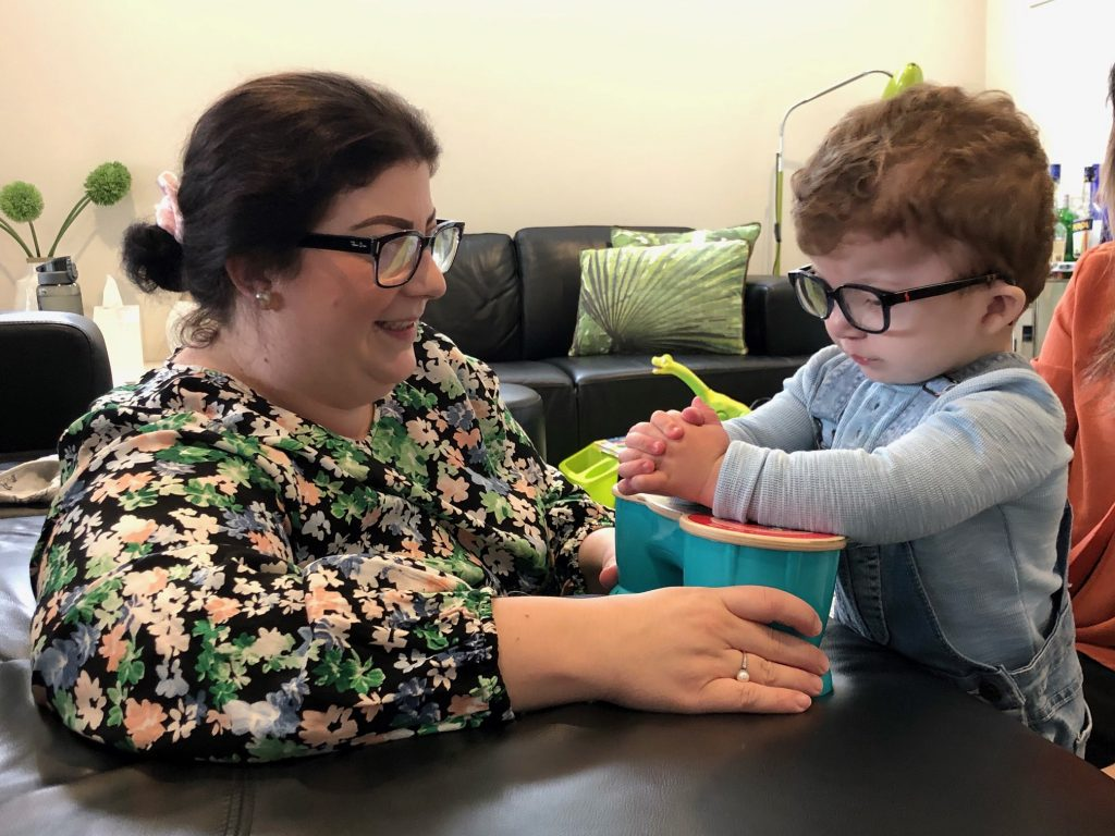 Young customer Henry and his mum Leanne. Henry is wearing a blue tshirt and denim overalls and is playing with a switch toy. Leanne is smiling and wearing a floral blouse.
