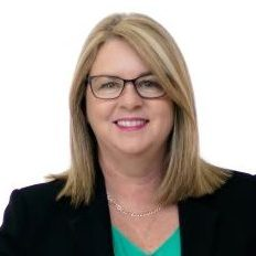Woman in suit and glasses looks at camera smiling